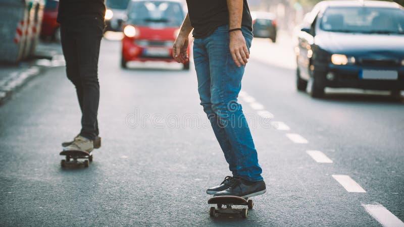 Proreiter-Fahrrochen des Skateboards zwei durch Autos auf Straße lizenzfreie stockfotos