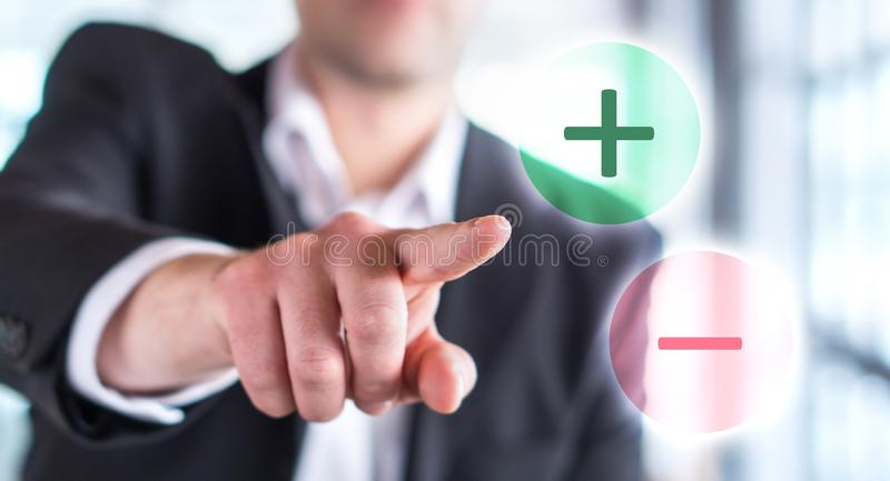 Pros and cons concept. Business man touching plus or minus. stock images