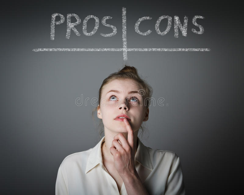 Pros and cons. Hesitation. Girl in white is thinking. Pros and cons concept. Young slim woman royalty free stock photo