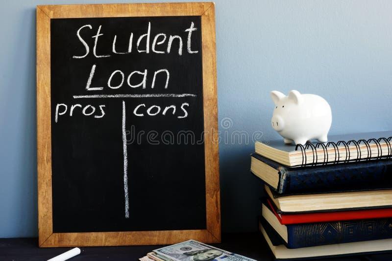 Pros del préstamo del estudiante - y - contra manuscrito en una pizarra fotografía de archivo libre de regalías