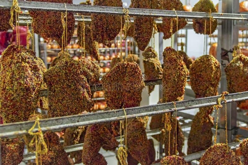 Prosciutti affumicati della carne con le spezie e le erbe che appendono sul contatore Carni affumicate tradizionali: prosciutto,  fotografie stock libere da diritti