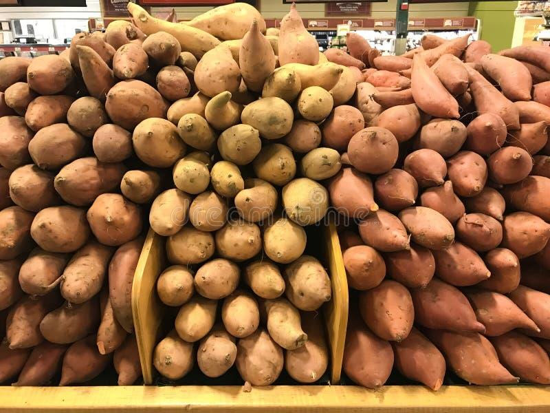 Prosciutti e patate dolci ammassati al mercato immagine stock libera da diritti