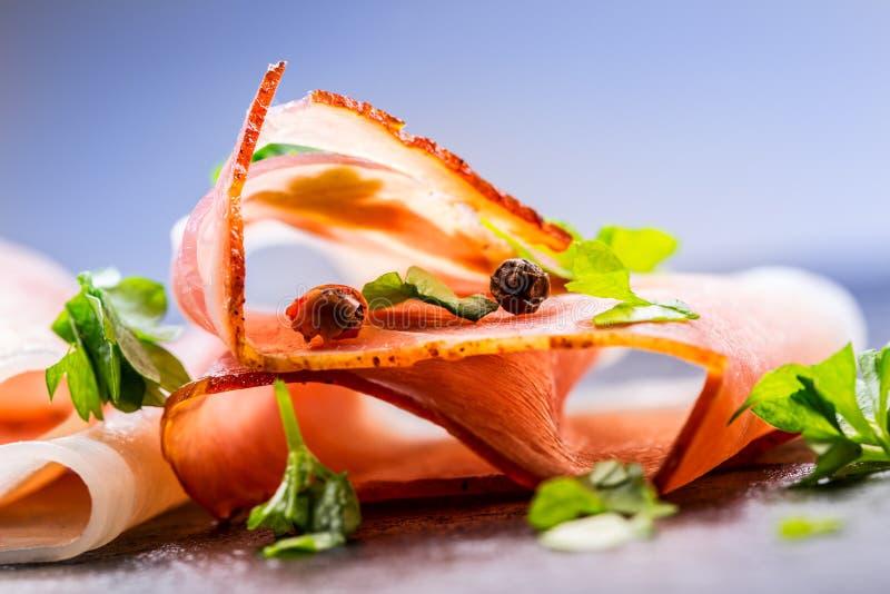 prosciutto 卷曲的切片可口熏火腿用荷兰芹在花岗岩板离开 与香料西红柿garli的Prosciuto 库存图片