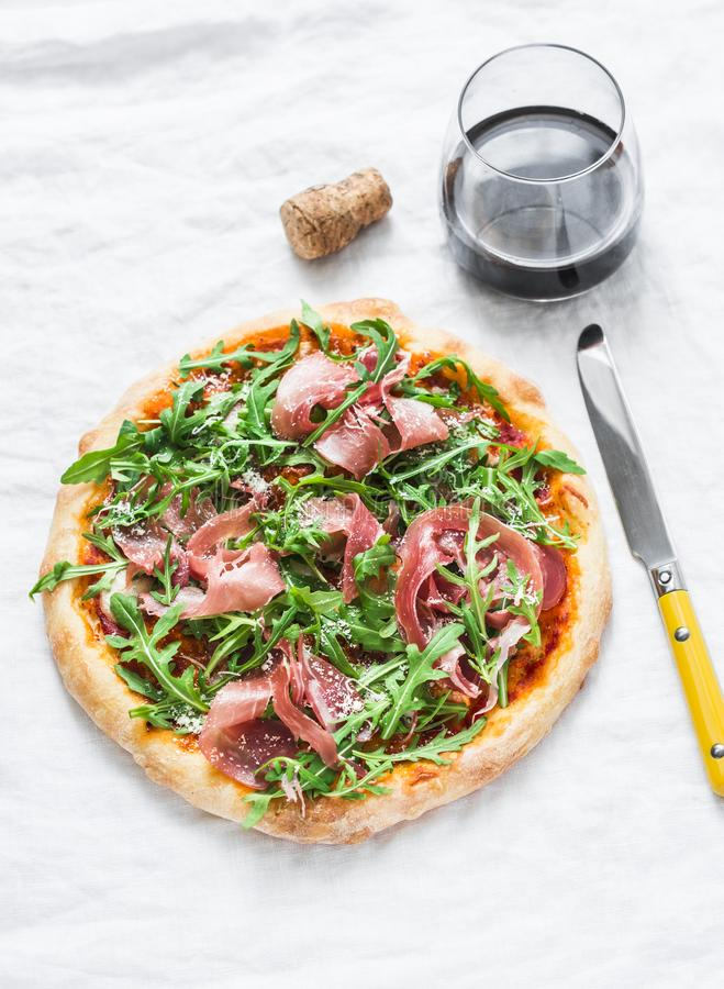 Prosciutto arugula homemade pizza and a glass of red wine on light background, top view. Delicious appetizers stock images