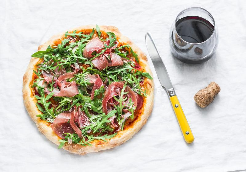 Prosciutto arugula homemade pizza and a glass of red wine on light background, top view. Delicious appetizers royalty free stock photography