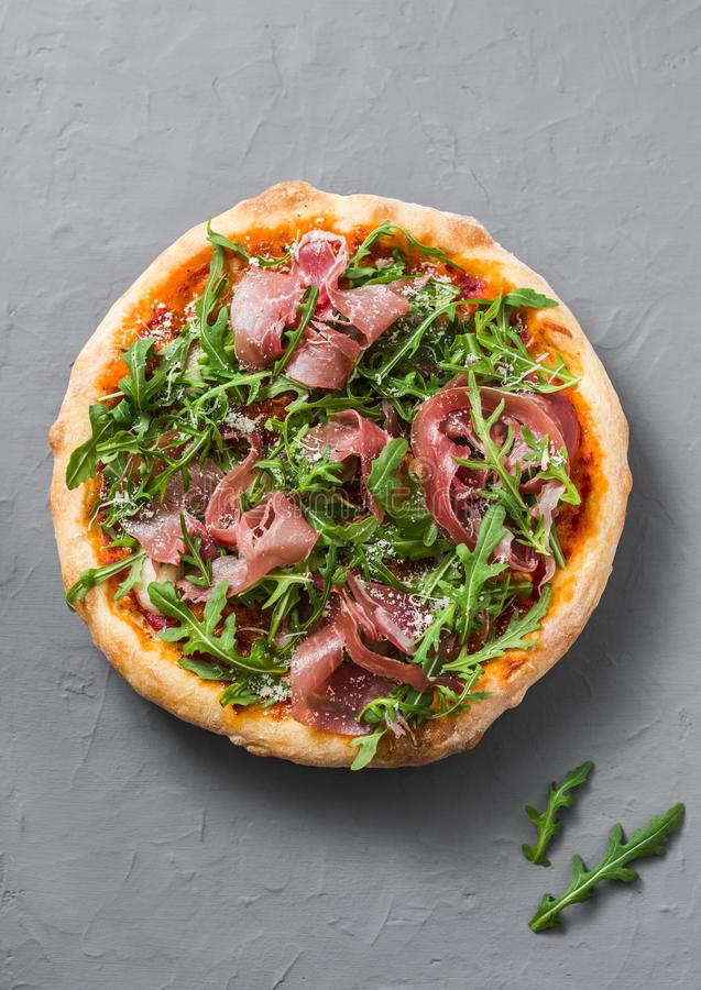 Prosciutto arugula homemade pizza on grey background, top view. Delicious appetizers in mediterranean style. royalty free stock images