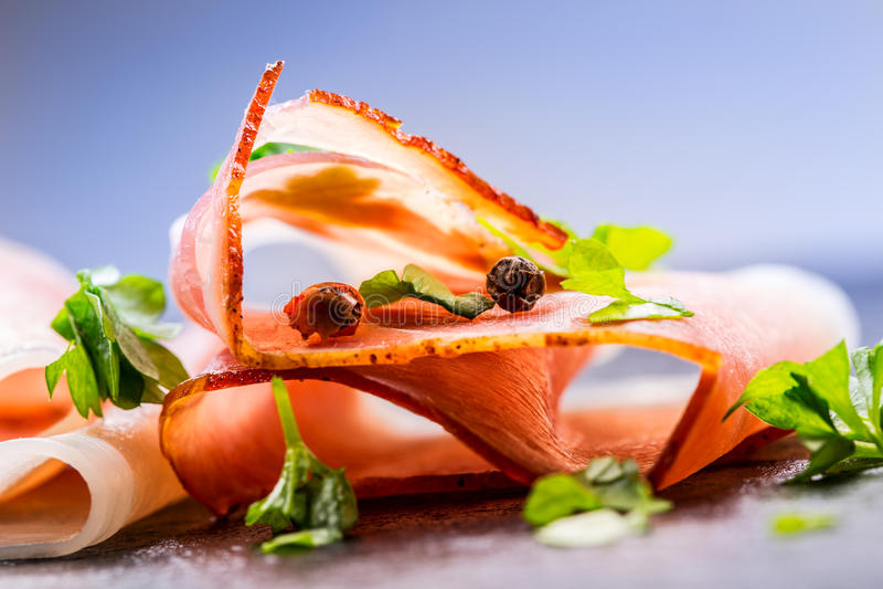 prosciutto As fatias onduladas de Prosciutto delicioso com salsa saem na placa do granito Prosciuto com o garli dos tomates de ce imagem de stock