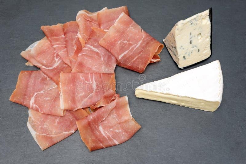Prosciutto avec sur la table en pierre grise Jambon de Serrano et fromage de camembert image stock