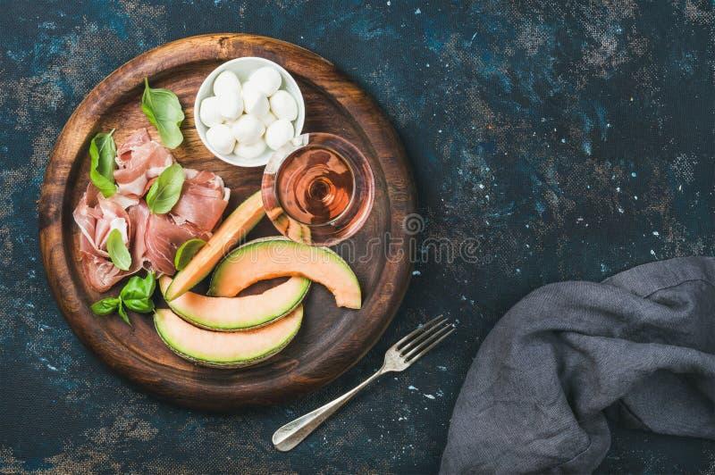 Prosciutto, cantaloupmelonmelon, mozzarella och exponeringsglas av rosa vin arkivfoto