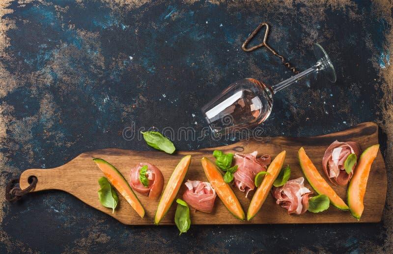 Prosciutto, cantaloupmelonmelon och vinexponeringsglas över mörk kryssfanerbakgrund royaltyfria bilder