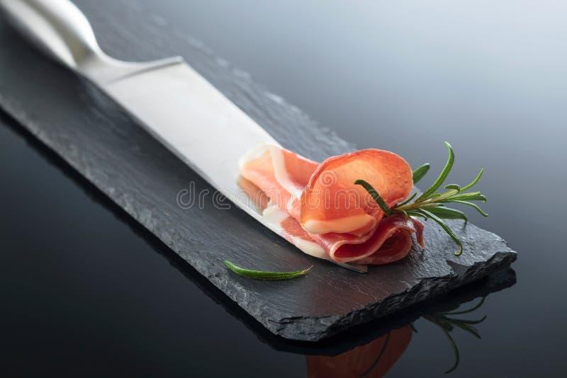 Prosciutto com alecrins e faca de cozinha fotos de stock royalty free