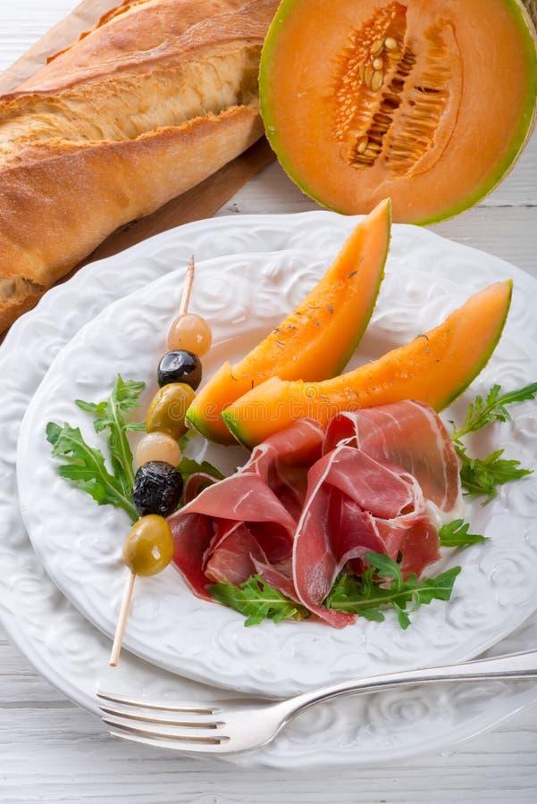 Prosciutto con il melone e le olive immagini stock