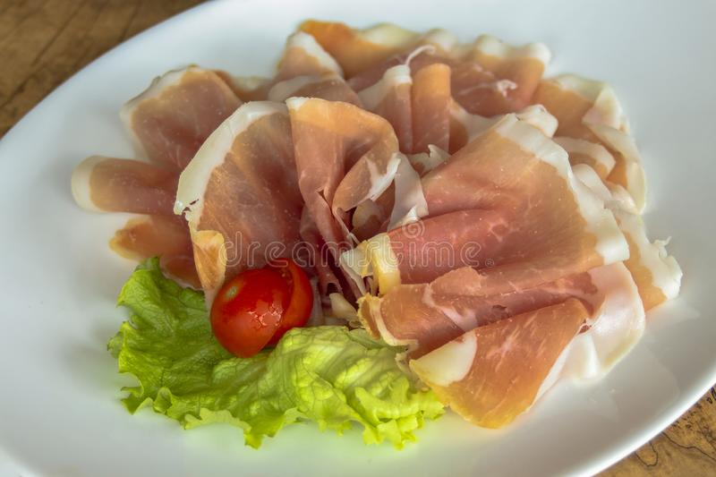 Cold appetizer - Prosciutto ham, on a leaf of green salad, garnished with cherry tomato. Served in a white dish. Closeup. royalty free stock image