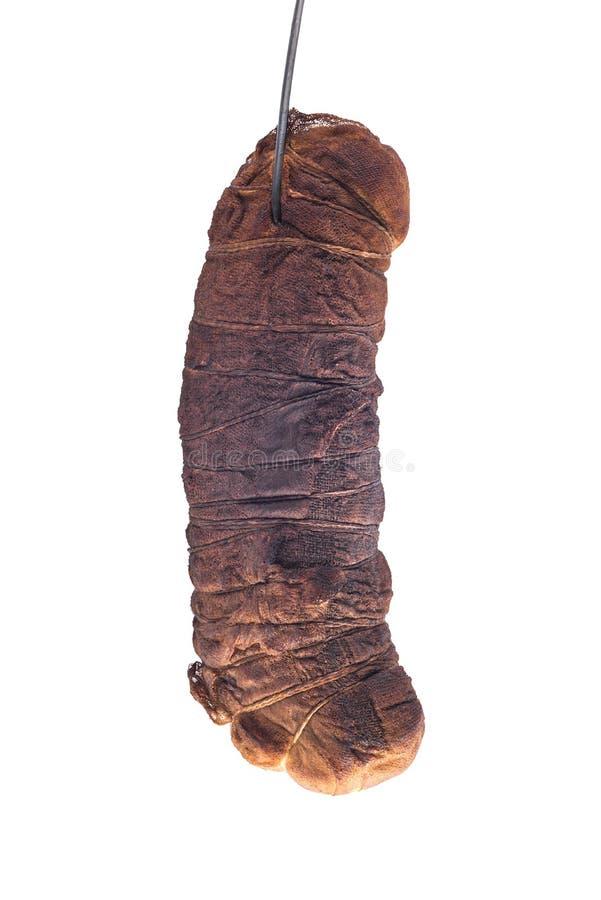 Prosciutto della carne di maiale avvolto in garza isolata su fondo bianco, appendente sul gancio del metallo, elemento tagliato d immagini stock