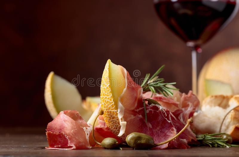 Prosciutto di Parma con il melone, i capperi ed i rosmarini immagine stock