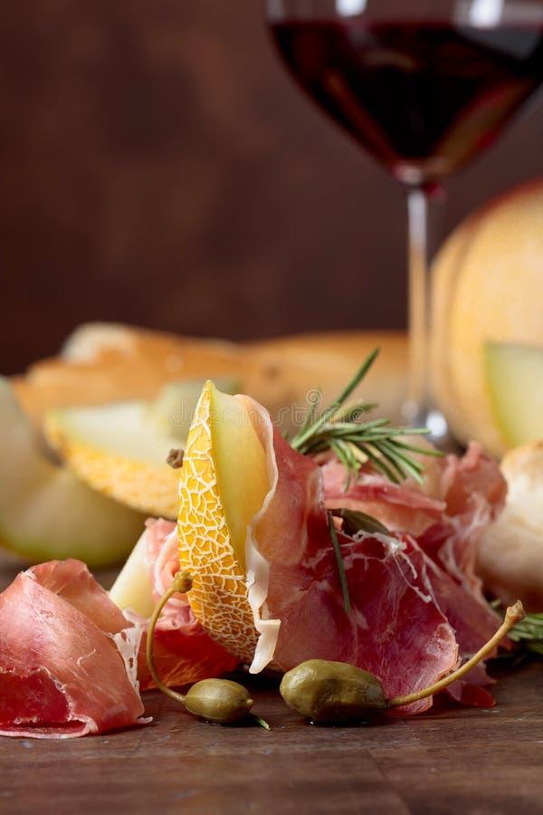 Prosciutto di Parma con il melone, i capperi ed i rosmarini su una vecchia tavola di legno fotografie stock