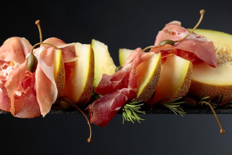 Prosciutto di Parma con il melone, i rosmarini ed i capperi su un fondo nero fotografia stock libera da diritti