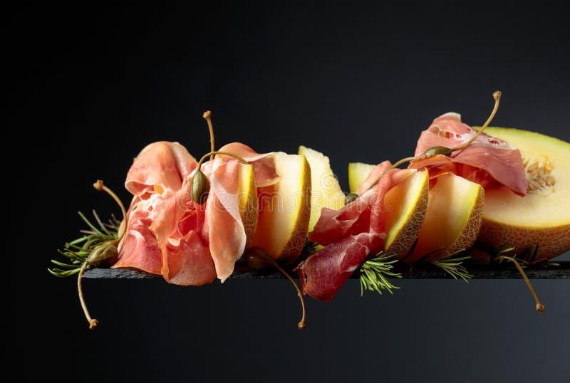 Prosciutto di Parma con il melone, i rosmarini ed i capperi su un fondo nero fotografia stock