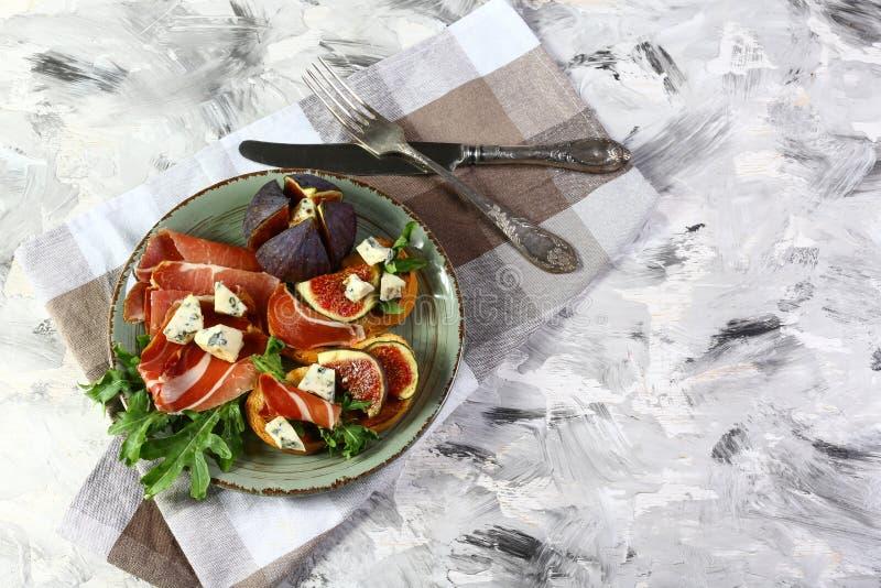 Prosciutto di Parma del pane tostato della frutta dei fichi con il formaggio di dorblyu con la muffa blu sulla tavola Frutta fres fotografie stock