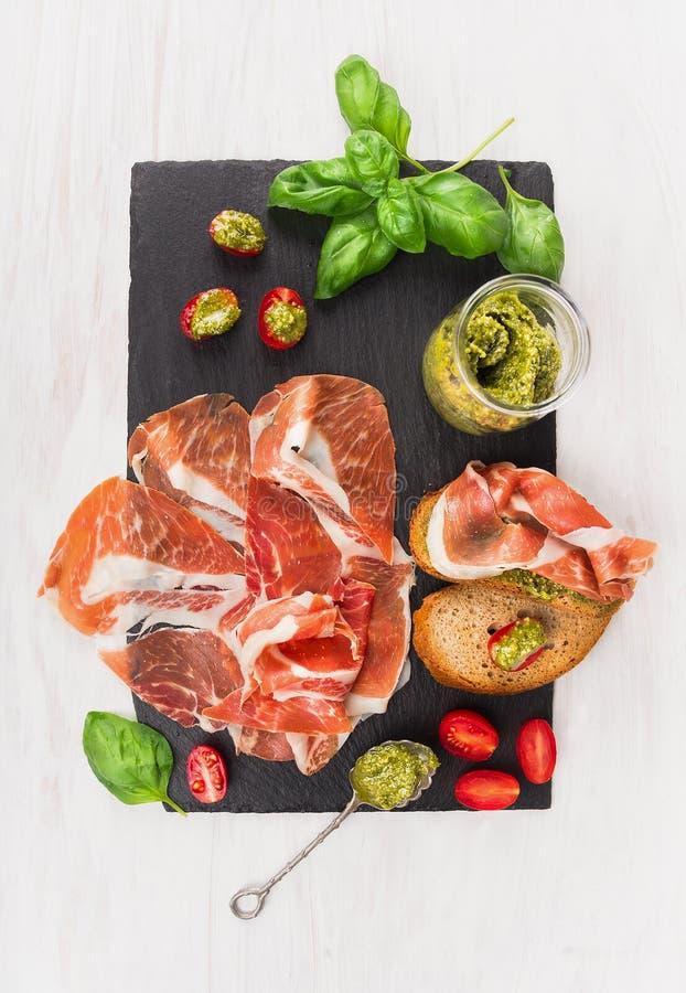 Prosciutto di prosciutto di Parma con pane, il pesto del basilico ed i pomodori sull'ardesia fotografia stock libera da diritti