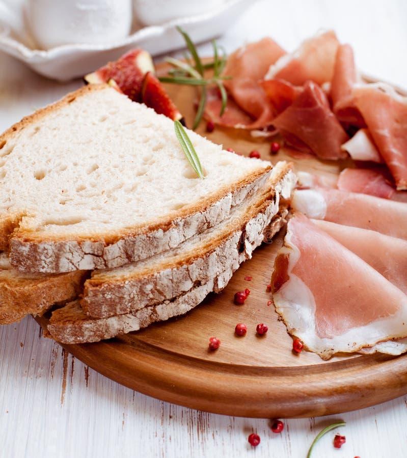 Prosciutto e pane asciutti curati sulla scheda di legno fotografia stock