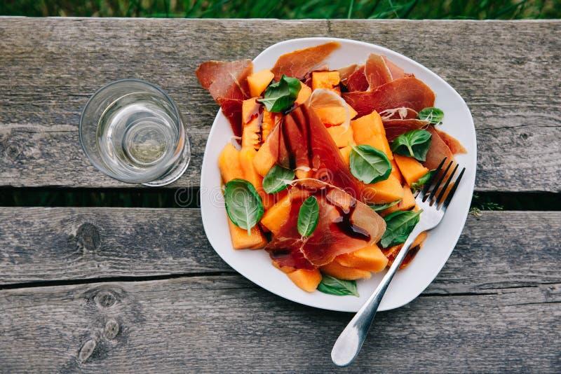 Prosciutto en meloensalade met basilicum en balsemieke saus stock afbeeldingen