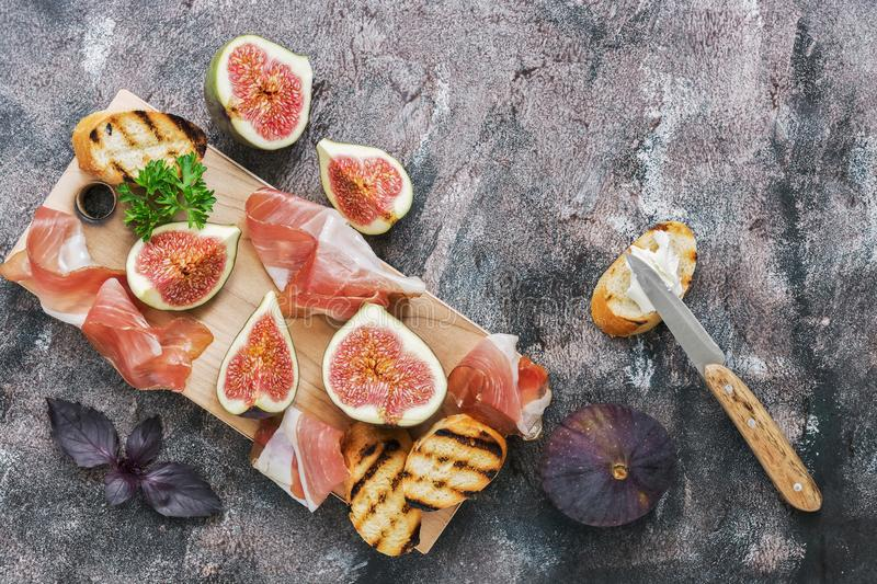Prosciutto with figs on a rustic background. Flat lay. royalty free stock image