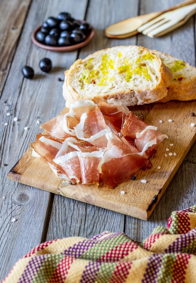 Prosciutto ham and bread on a wooden background. Italian cuisine. Rustic style royalty free stock photography