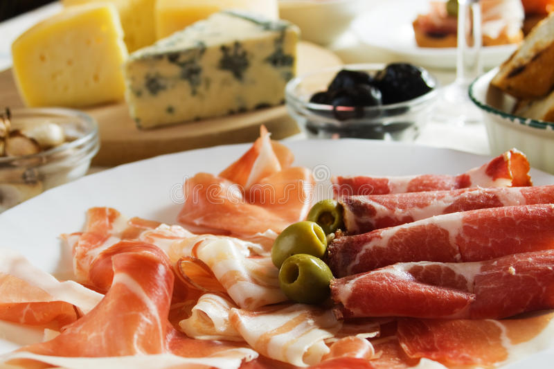 Prosciutto, italian cured ham. With green olives royalty free stock images