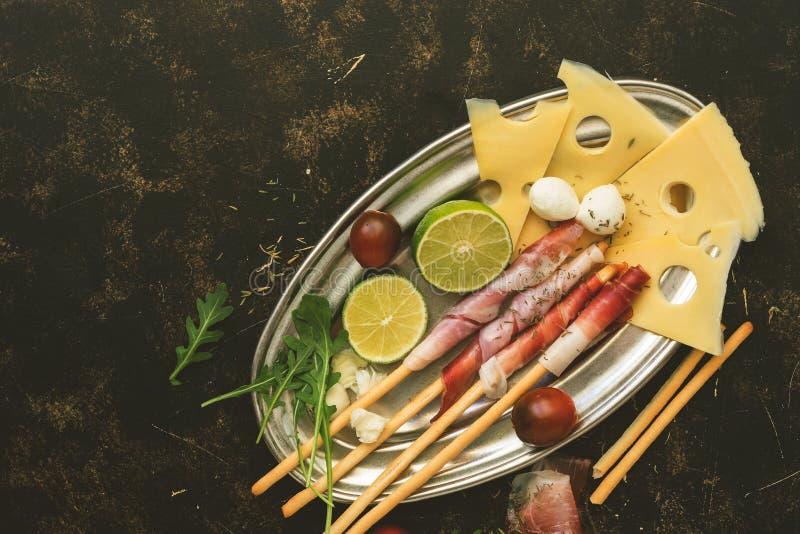 Prosciutto, Maasdam ser i mozzarella, wapno, czarny czereśniowy pomidor, arugula w metalu talerzu na ciemnym nieociosanym tle _ fotografia royalty free