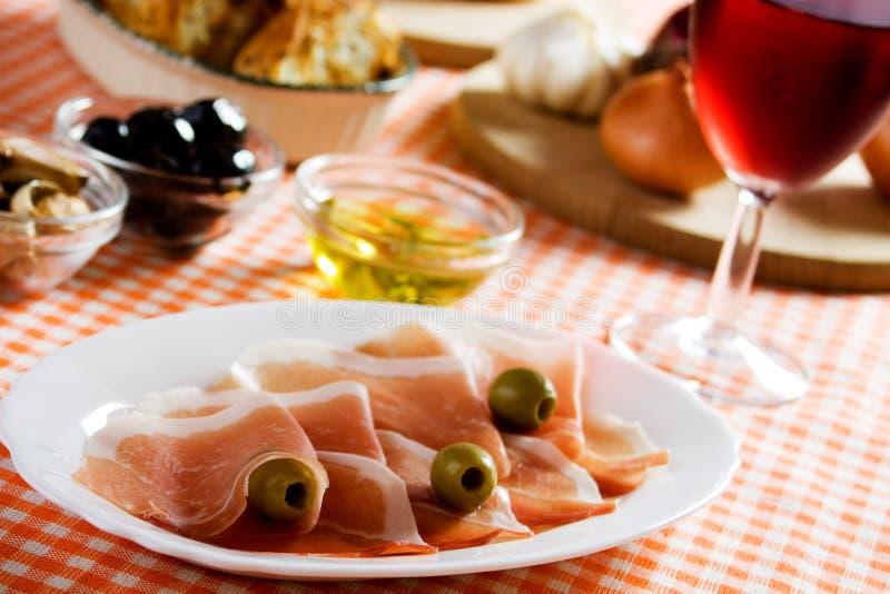 Prosciutto met olijven stock fotografie