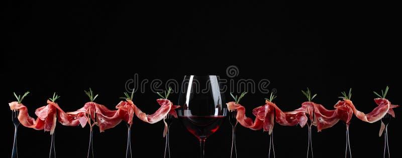 Prosciutto mit Rosmarin und Glas Rotwein auf einem schwarzen backgr lizenzfreie stockbilder
