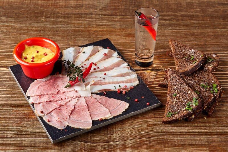 Prosciutto ou presunto de parma cortado, pão com sal, mostarda e um vidro da vodca com pimenta picante em uma tabela de madeira d foto de stock royalty free