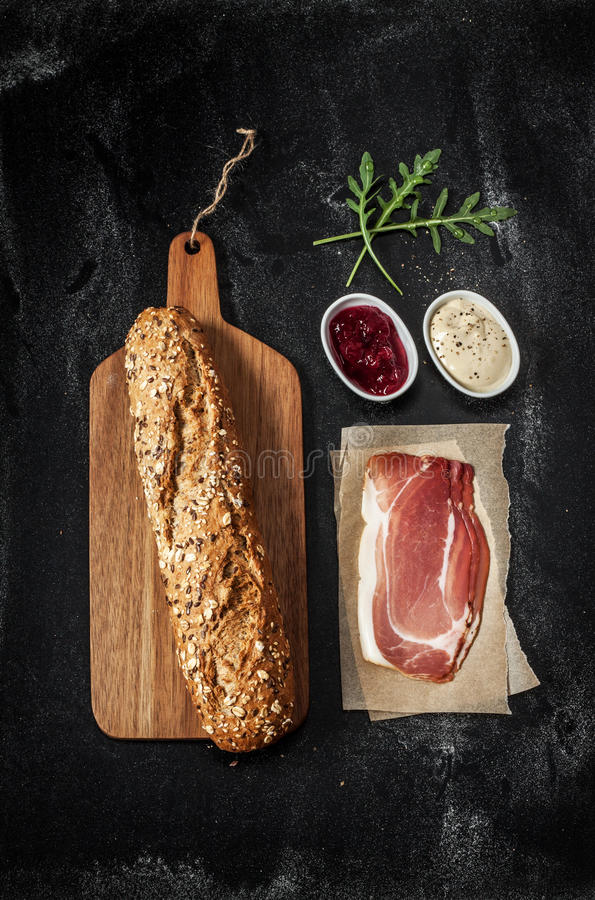 Prosciutto (Parma baleron) kanapka przepis - składniki na czerni zdjęcia stock