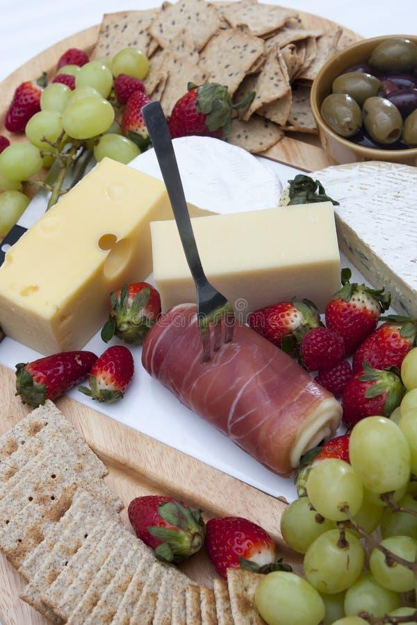 Prosciutto, patatine fritte e cracker, olive, uva, fragole e formaggio fotografia stock