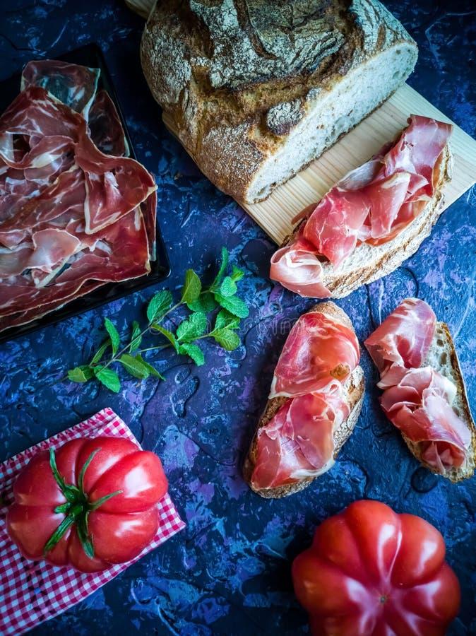 Prosciutto, pomodoro, pane ed erbe in composizione su fondo scuro fotografia stock