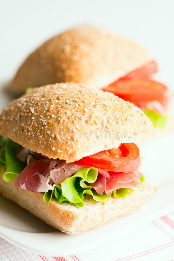 Prosciutto sandwiches with tomato and arugula on table stock photo