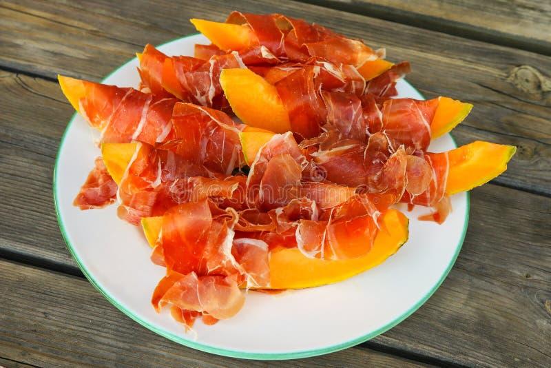 Prosciutto servi avec le melon frais de cantaloup images libres de droits