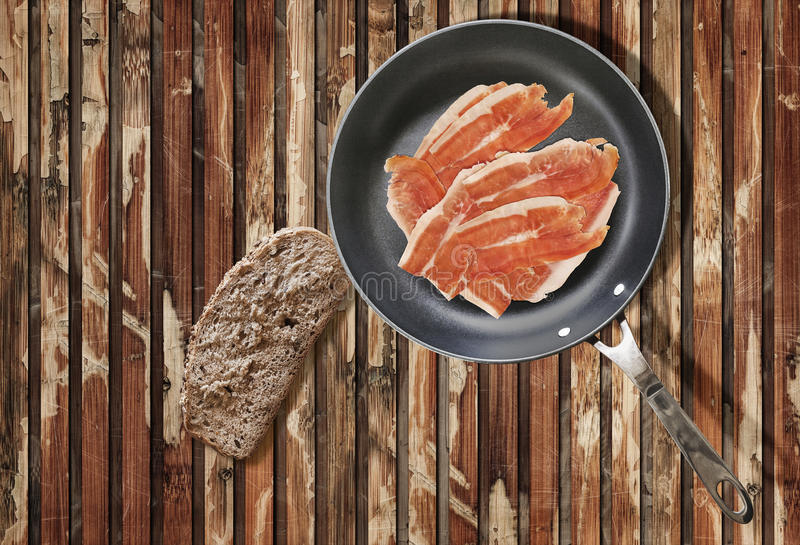 Prosciutto Smoked Ham Rashers in Frying Pan with Slice of Bread on very Old Cracked Wooden Table royalty free stock images