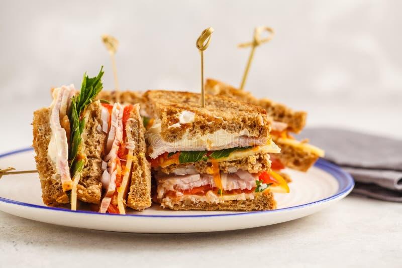 Prosciutto, verdure e panini di club del formaggio su un piatto bianco, whi fotografia stock
