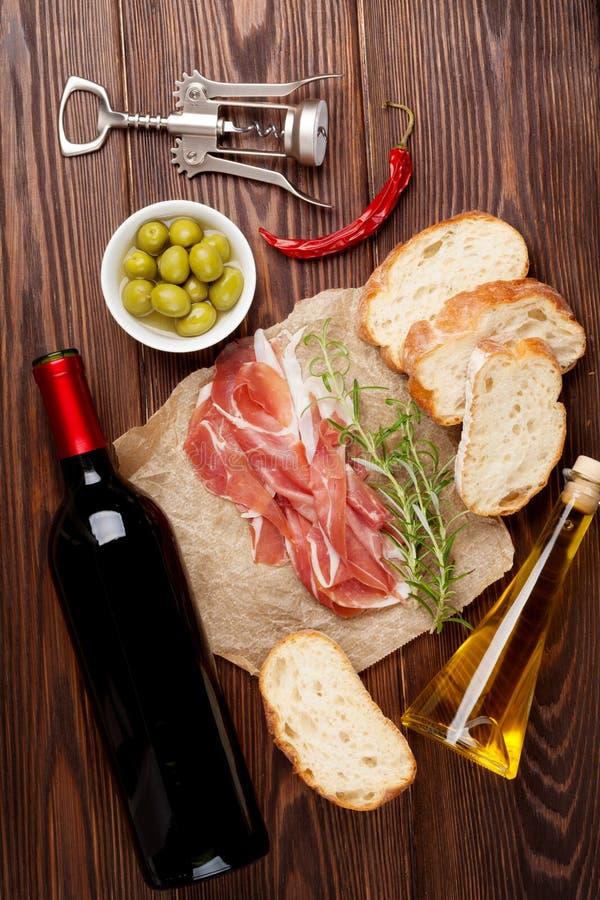 Prosciutto, vino, aceitunas, parmesano y aceite de oliva fotos de archivo