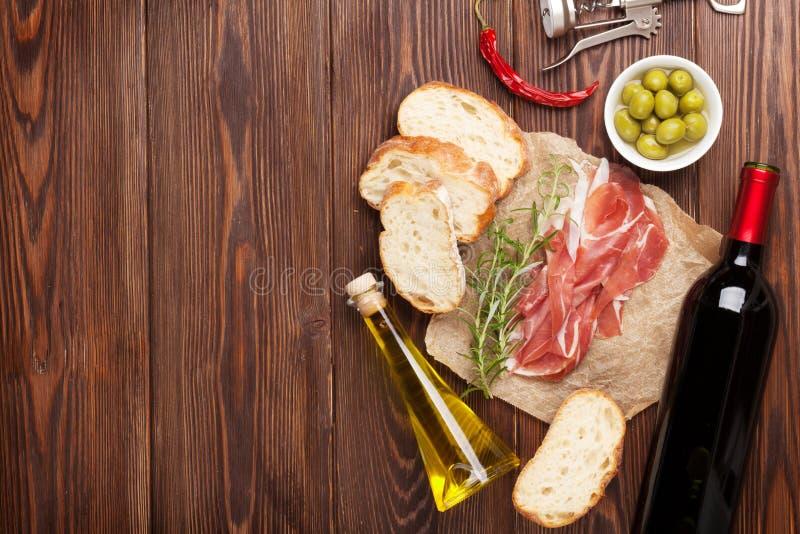 Prosciutto, vino, aceitunas, parmesano y aceite de oliva foto de archivo