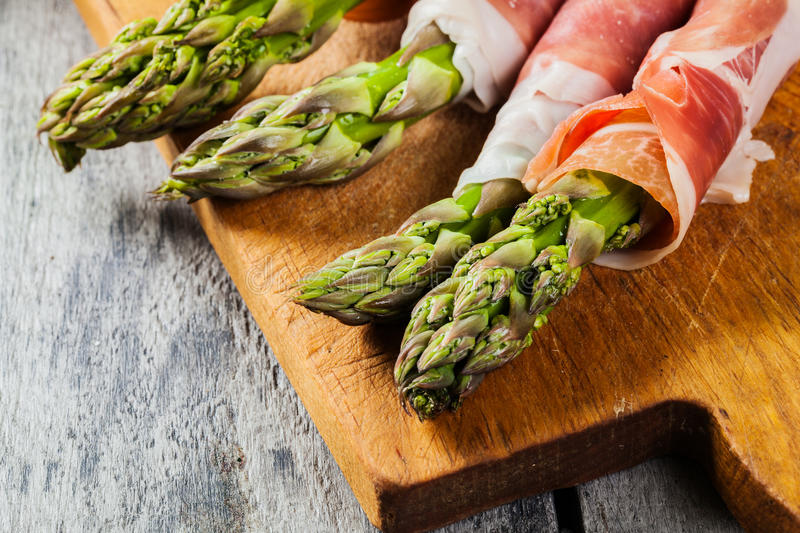 Prosciutto wrapped green asparagus. On a cutting board royalty free stock images