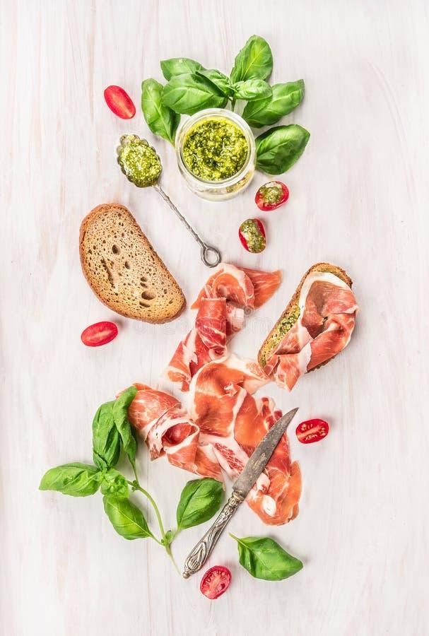 Prosciuttoskinka med rostat brödbröd, basilikapesto och tomater royaltyfri fotografi