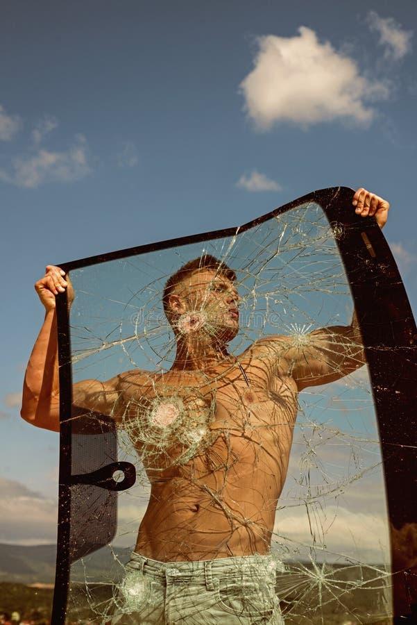 Prosecución de su ambición Vidrio agrietado del control del hombre fuerte Hombre del deporte con fuerza muscular Entrenamiento de fotos de archivo