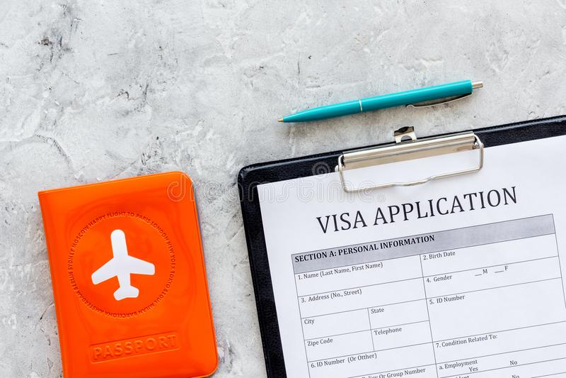 prosessing的签证 签证的注册 签证申请形式,笔,有飞机剪影的护照盖子在灰色 库存照片