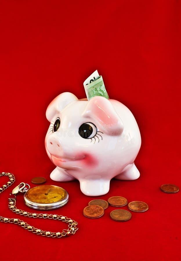 Prosiątka bank, monety i zegarek na czerwonym tle, zdjęcia stock