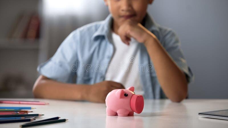 Prosiątko bank na stole w frontowej szkolnej chłopiec, planuje budżet, kieszeniowy pieniądze, finanse zdjęcia stock