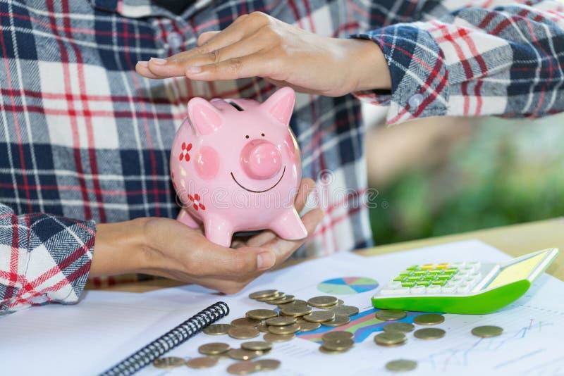 Prosiątko bank ochraniający rękami, oszczędzanie ochrona zdjęcie royalty free