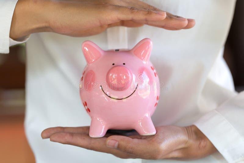 Prosiątko bank ochraniający rękami, oszczędzanie ochrona, Pieniężny hedging, zarządzanie ryzykiem zdjęcia royalty free